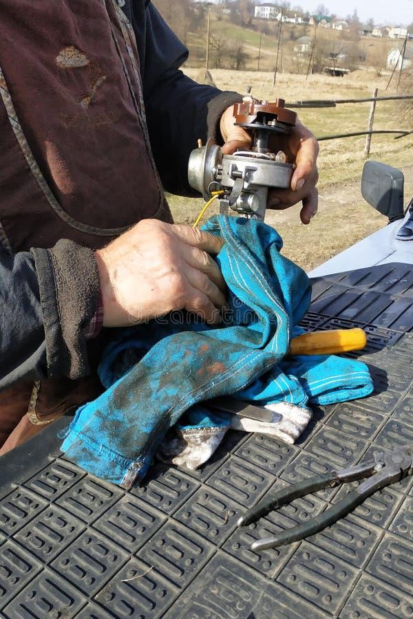 De autowerktuigkundige voert reparatie van de verdeler van ontsteking van de oude VAZ-merkauto uit stock foto's