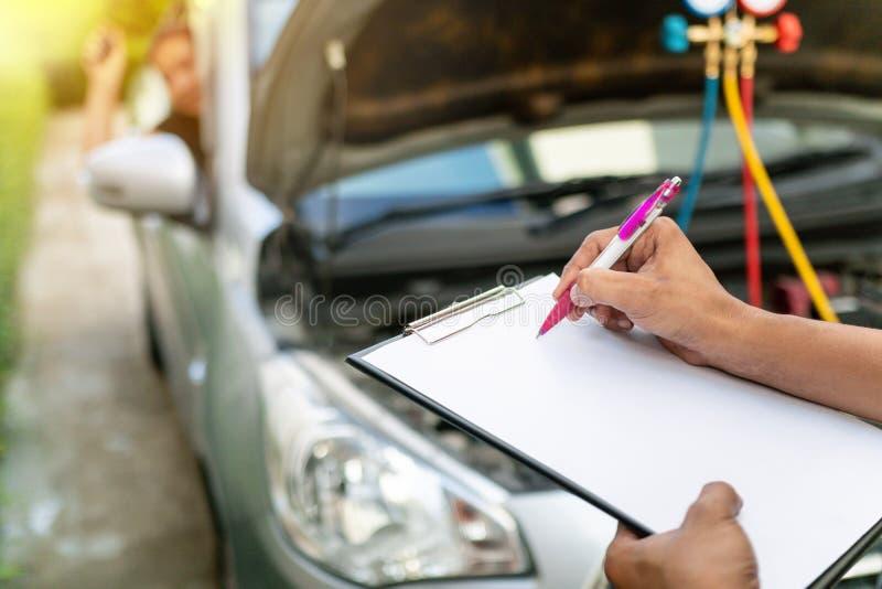 De autowerktuigkundige voert voertuigcontrole uit terwijl de de dienstadviseur Professionele nota's neemt, stock afbeelding