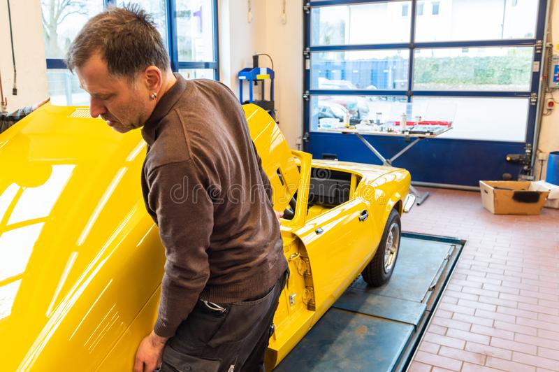De autowerktuigkundigen richten correct de bonnet wanneer het assembleren - Serie-Reparatieworkshop royalty-vrije stock fotografie