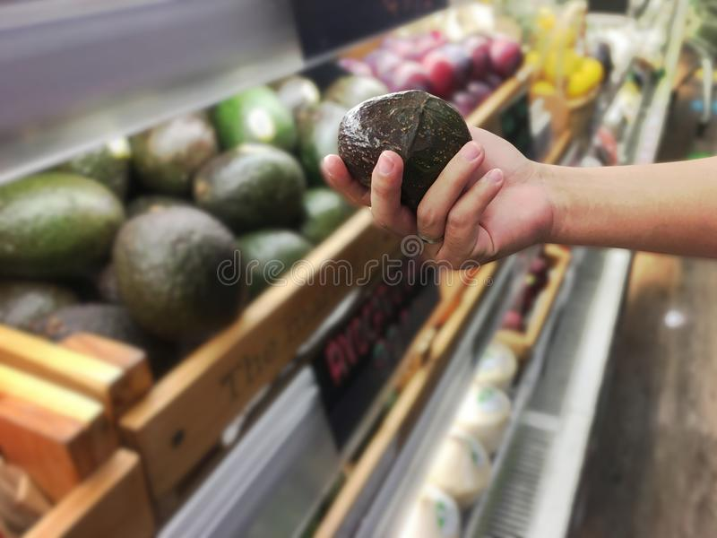 De avocado van de de handholding van de vrouw van de plank in de supermarkt stock afbeeldingen