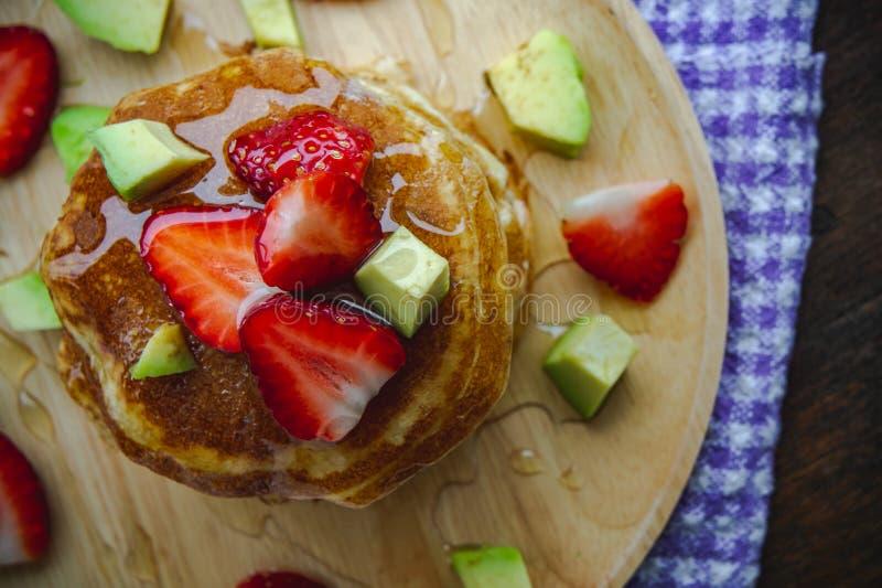De avocadofruit van de pannekoekaardbei en het zoete dessert van de honingsstroop op het houten eigengemaakte dessert van de lijs stock afbeeldingen