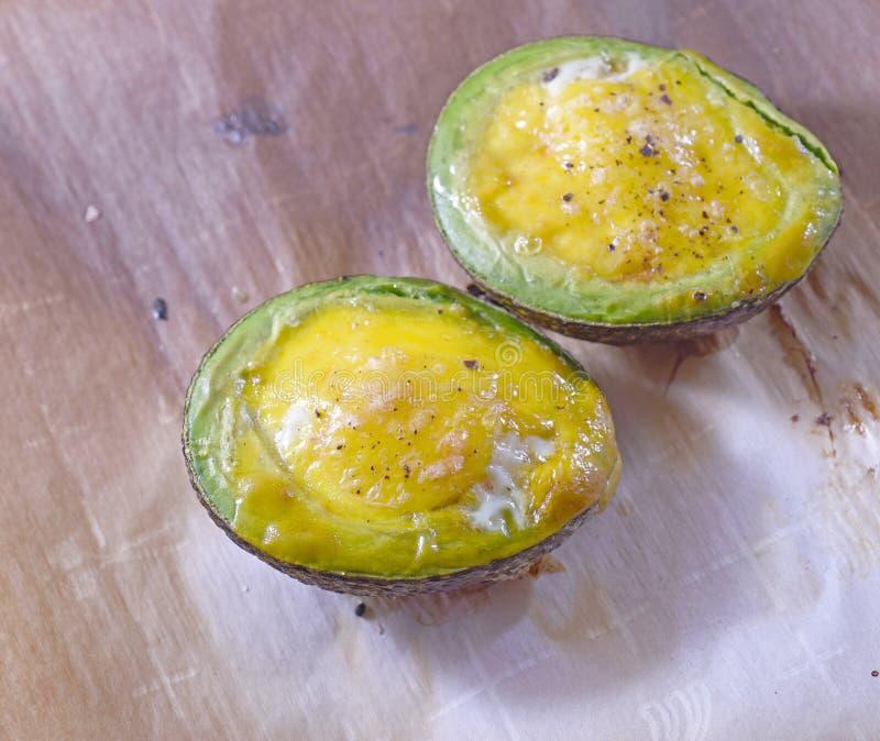 De avocadohelften met eieren worden gebakken dat stock foto