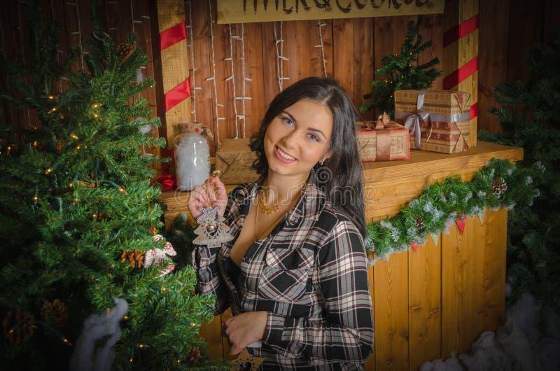In de avond een mooi meisje dichtbij de Kerstboom royalty-vrije stock afbeeldingen