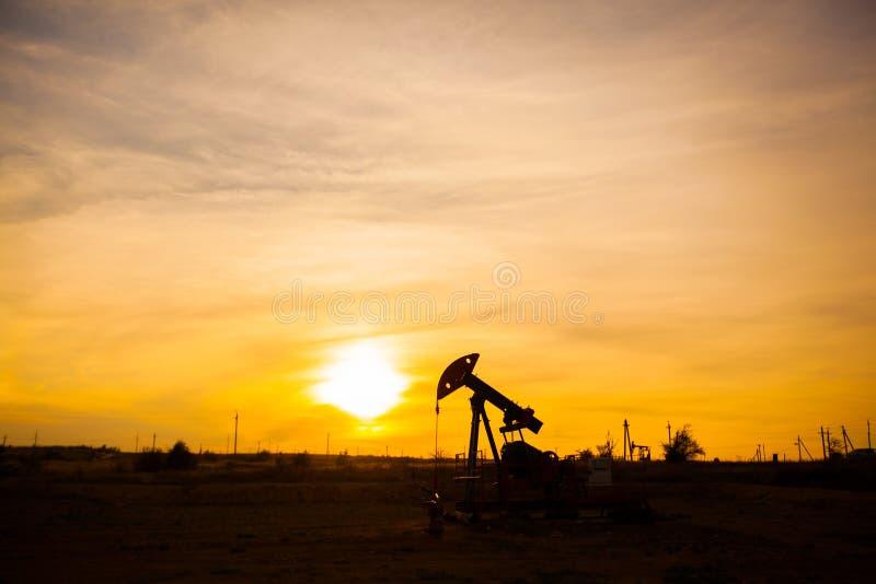 In de avond, het overzicht van de oliepomp De oliepomp, industrieel materiaal De olieveldplaats, oliepompen loopt stock foto