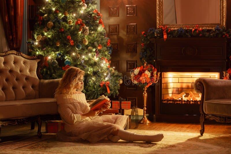 De avond van Kerstmis De jonge mooie blondevrouw las boek in klassieke flats een open haard, verfraaide boom royalty-vrije stock fotografie