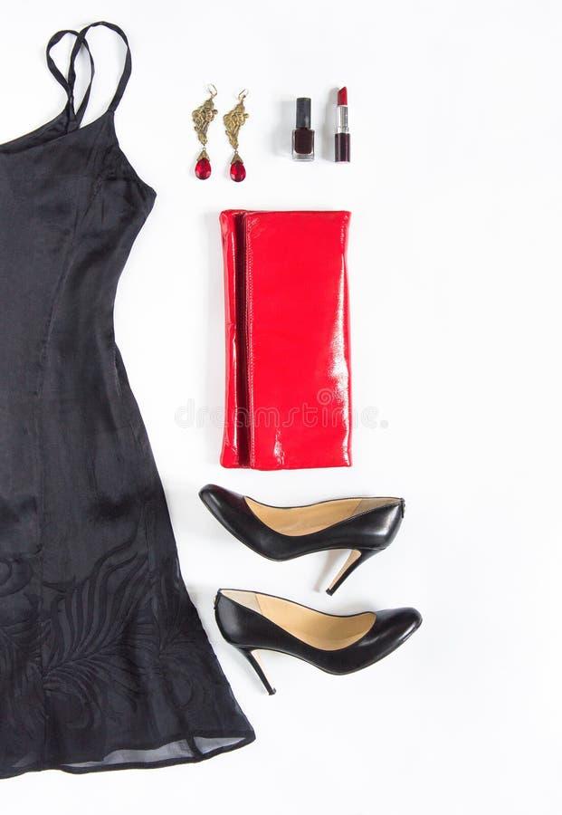 De avondjurkuitrusting, nacht kijkt uit op witte achtergrond Weinig zwarte kleding, rode koppeling, zwarte schoenen, oorringen, l royalty-vrije stock foto's