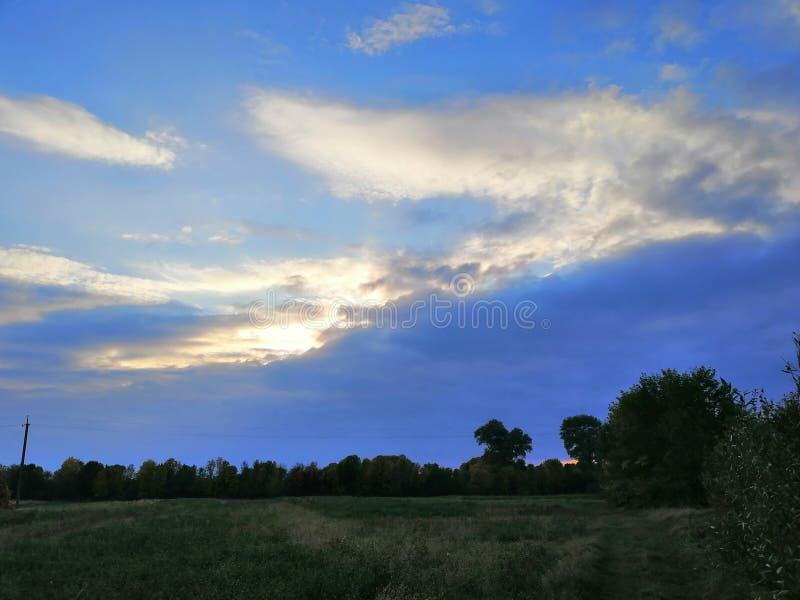 De avondzon verborg achter de wolken stock afbeelding