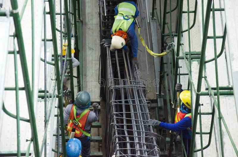 De Aziatische bars van het metaalstaven van de mensenarbeider breiende in kaderversterking voor het concrete gieten bij bouwwerf stock afbeelding