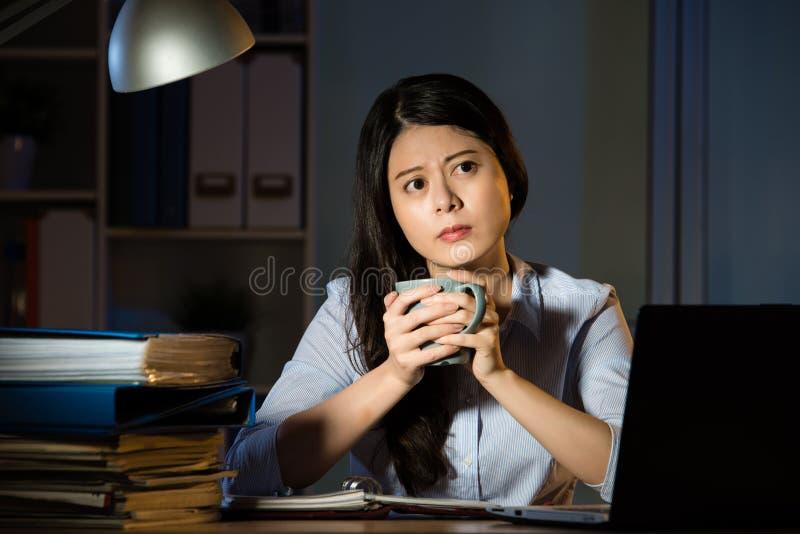 De Aziatische bedrijfsvrouw drinkt koffie het werk laat overwerk - nacht stock fotografie