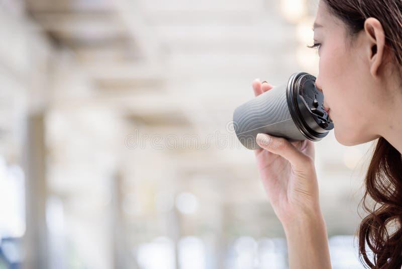 De Aziatische bedrijfsvrouw heeft het drinken van een kop van koffie royalty-vrije stock foto