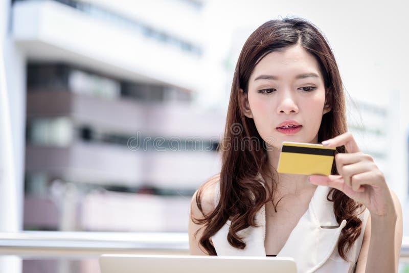 De Aziatische bedrijfsvrouw heeft het winkelen en het kopen met kredietauto stock foto's