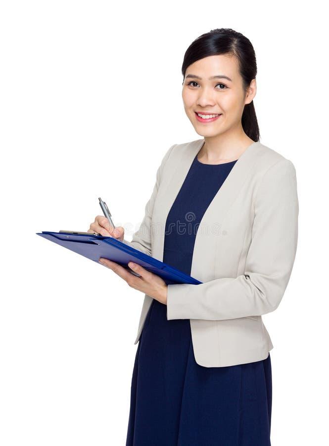 De Aziatische bedrijfsvrouw noteert informatie over dossierstootkussen royalty-vrije stock foto's