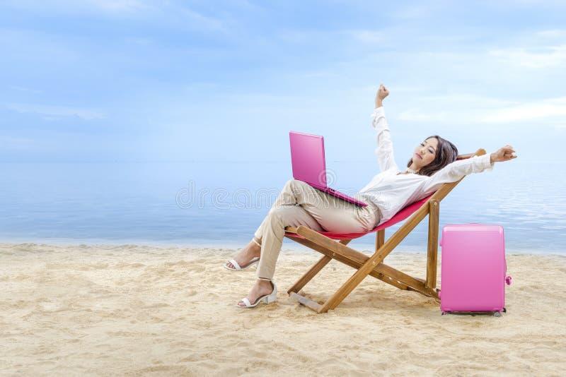 De Aziatische bedrijfsvrouw ontspant wanneer het werken met laptop zitting in de ligstoel aan strand royalty-vrije stock afbeeldingen