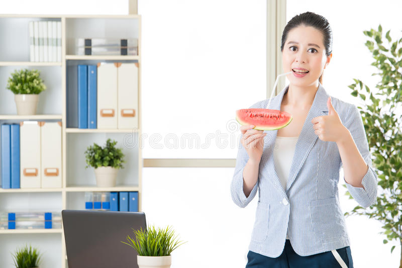 De Aziatische bedrijfsvrouw voelt verfrissing na het drinken van watermeloen royalty-vrije stock foto's
