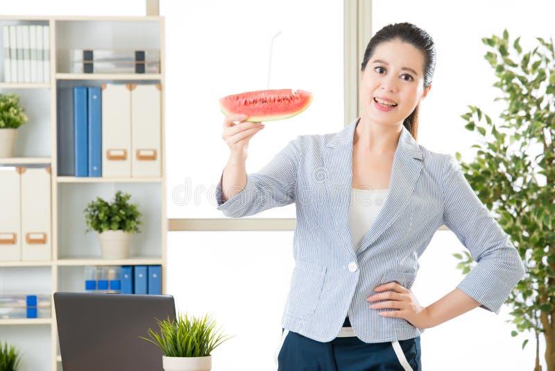 De Aziatische bedrijfsvrouw voelt verfrissing na het sap van de pogingswatermeloen stock afbeeldingen
