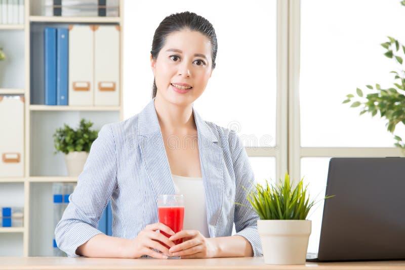 De Aziatische bedrijfsvrouw voelt verfrissing na het sap van de pogingswatermeloen stock afbeelding