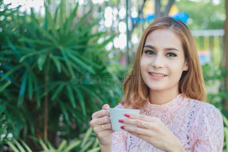 De Aziatische bedrijfsvrouw werkt en drinkt koffie op openlucht stock fotografie