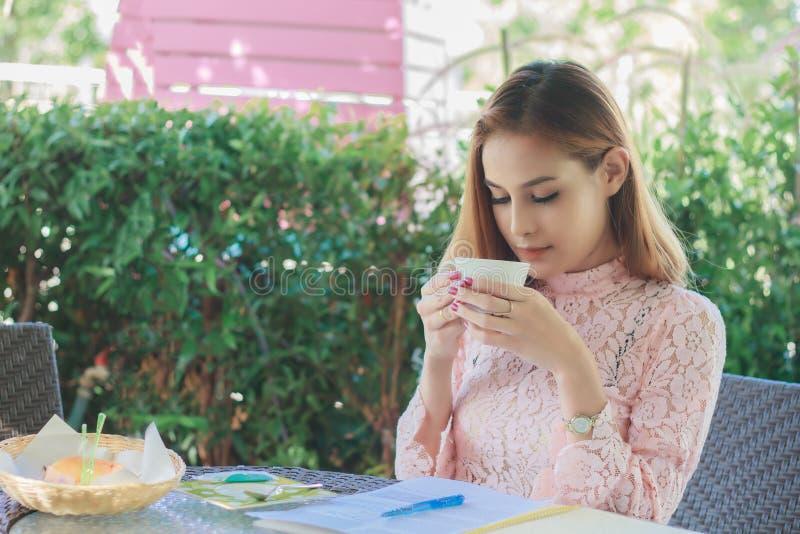 De Aziatische bedrijfsvrouw werkt en drinkt koffie op openlucht stock foto