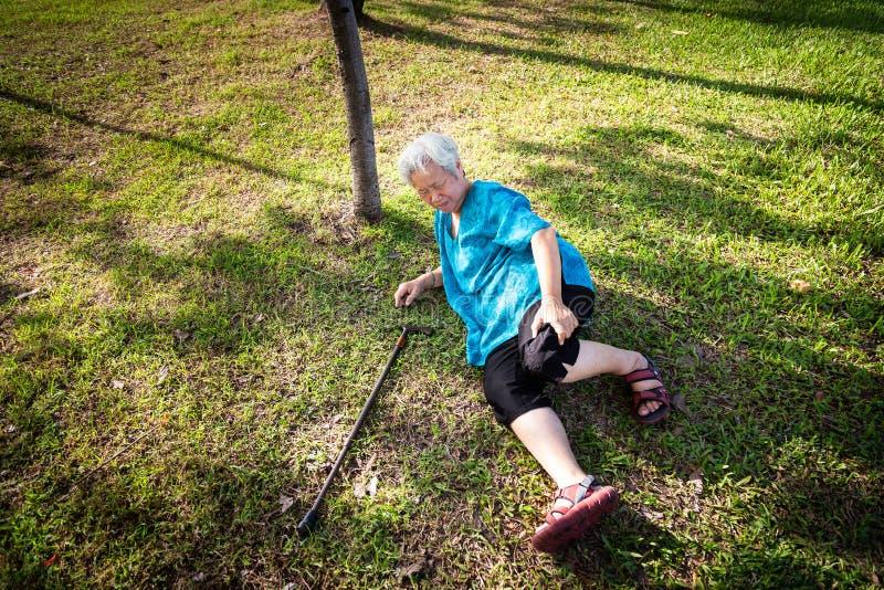 De Aziatische bejaarde mensen met wandelstok op vloer na het vallen neer in de zomer openluchtpark, zieke hogere vrouw vielen aan stock foto's