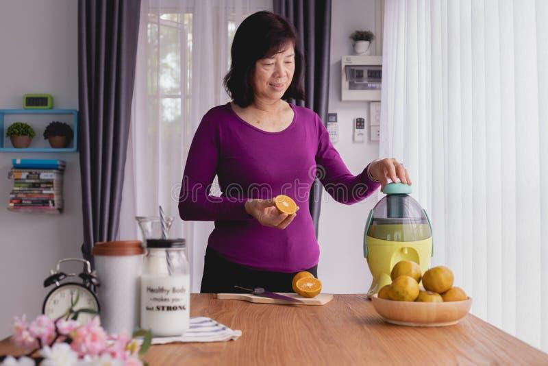 De Aziatische bejaarden maken jus d'orange door mixer, voorbereidend voedsel stock afbeelding