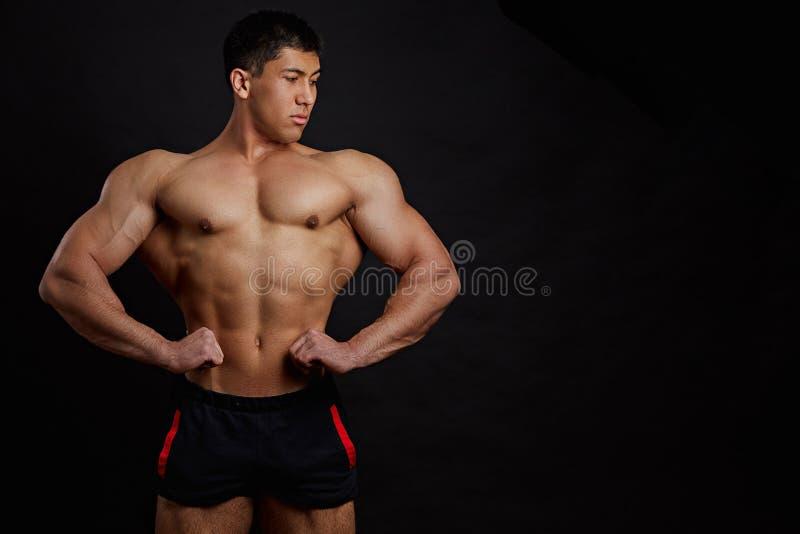 De Aziatische bodybuilder toont zijn spieren stock fotografie