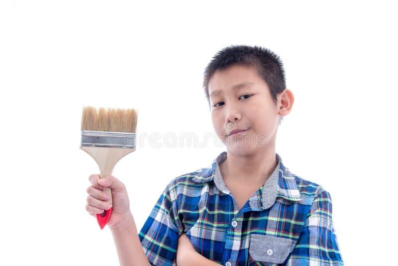 De Aziatische borstel van de jongensholding in zijn hand op wit stock fotografie
