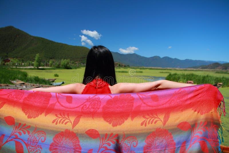 De Aziatische Chinese schoonheid in rode kleding geniet van het vreedzame en gelukkige leven bij het grasmeer van Yunnan Lugu royalty-vrije stock fotografie