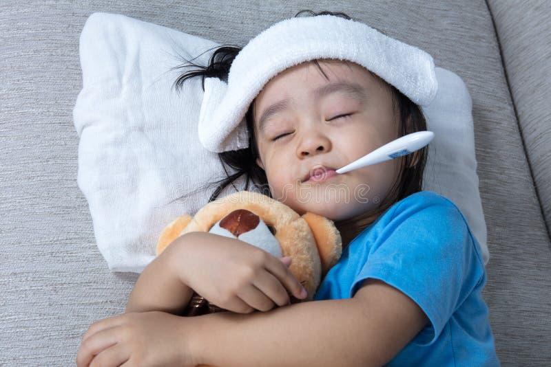 De Aziatische Chinese teddybeer van de meisjesholding voor koortstemperatuur meas royalty-vrije stock fotografie