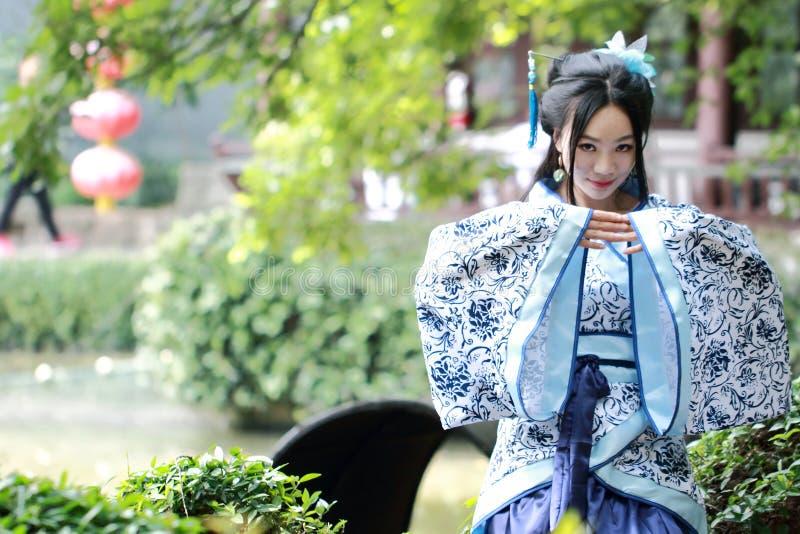 De Aziatische Chinese vrouw in traditionele Blauwe en witte Hanfu-kleding, spel in een beroemde tuin, zit op een oude steenstoel stock afbeeldingen