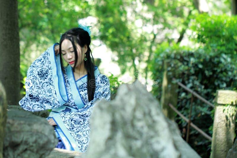 De Aziatische Chinese vrouw in traditionele Blauwe en witte Hanfu-kleding, spel in een beroemde tuin, zit op een oude steenstoel stock afbeelding