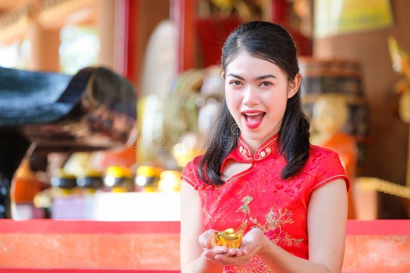 De Aziatische Chinese vrouw in Traditionele Chinees houdt Chinees geld stock afbeelding