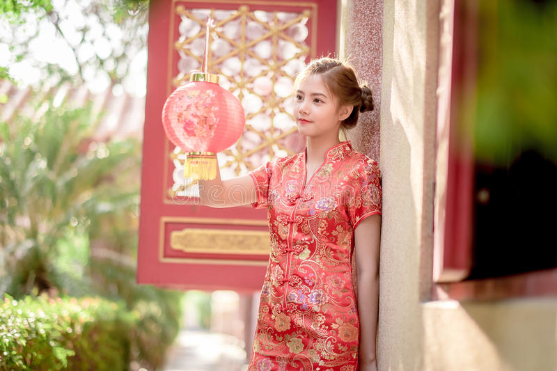 De Aziatische Chinese vrouw in Traditionele Chinees houdt rood document stock foto's