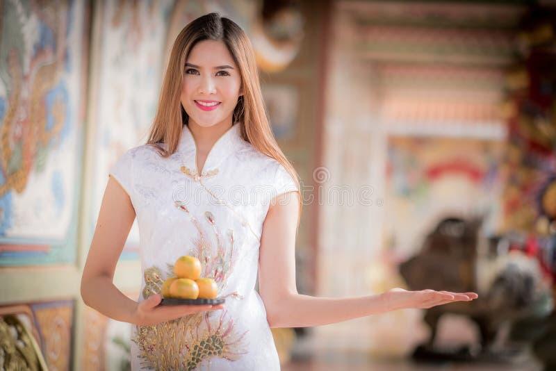 De Aziatische Chinese vrouw in Traditionele Chinese holdingssinaasappel betaalt aangaande royalty-vrije stock foto