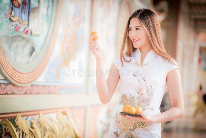 De Aziatische Chinese vrouw in Traditionele Chinese holdingssinaasappel betaalt aangaande royalty-vrije stock fotografie