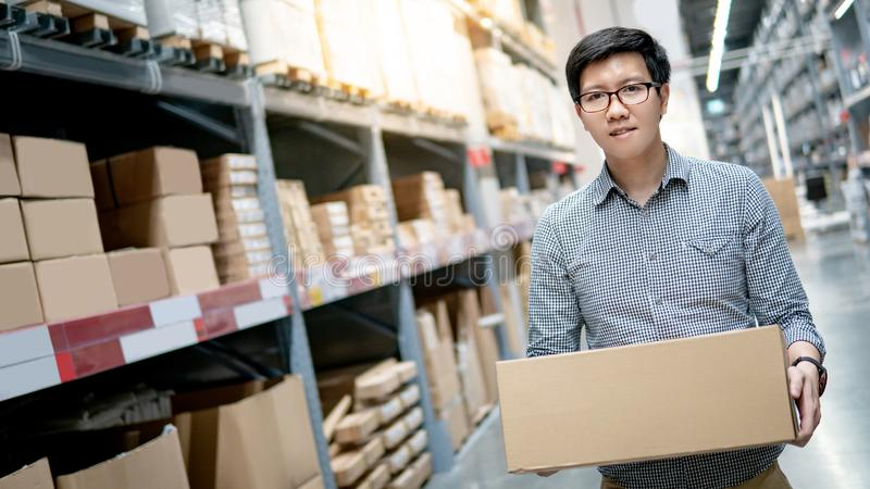De Aziatische doos van het mensen dragende karton in pakhuis royalty-vrije stock foto