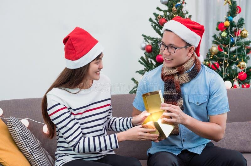 De Aziatische doos van de mensen open gouden gift met meisje op bank bij Kerstmispartij, vakantieviering Het concept van de verra stock foto