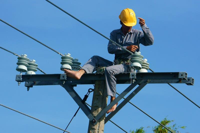 De Aziatische elektricien beklimt hoogte, het werk op elektrische pool royalty-vrije stock afbeelding
