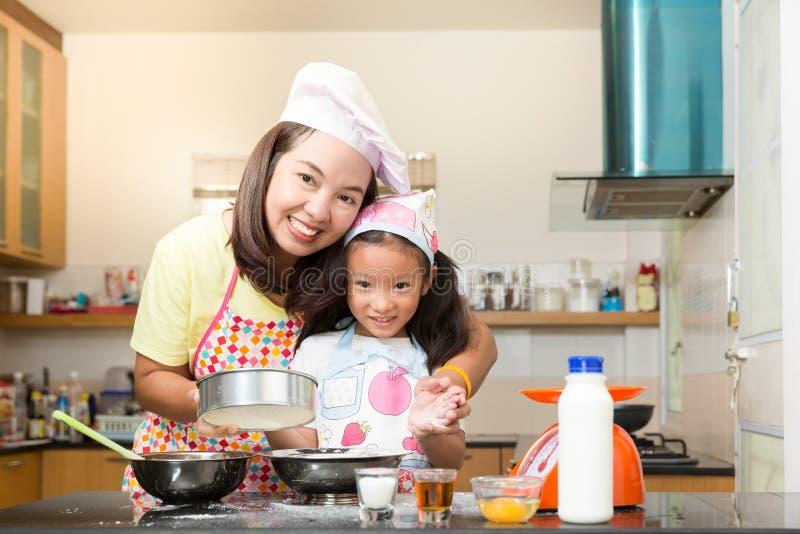 De Aziatische familie geniet van makend pannekoek, Aziatische moeder en dochter enj stock foto