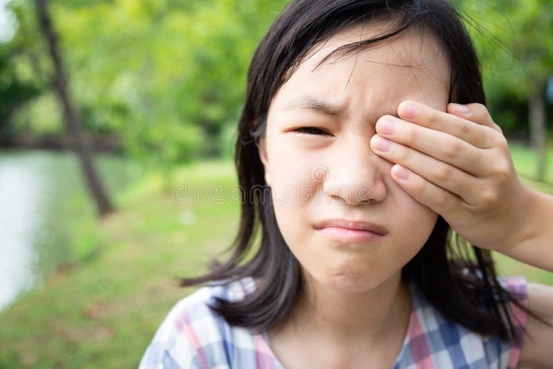De Aziatische geduldige pijnlijke, pijnlijke ogen van weinig kindmeisje, rakend, behandelend met hand of wrijvend haar oog, die o royalty-vrije stock afbeelding