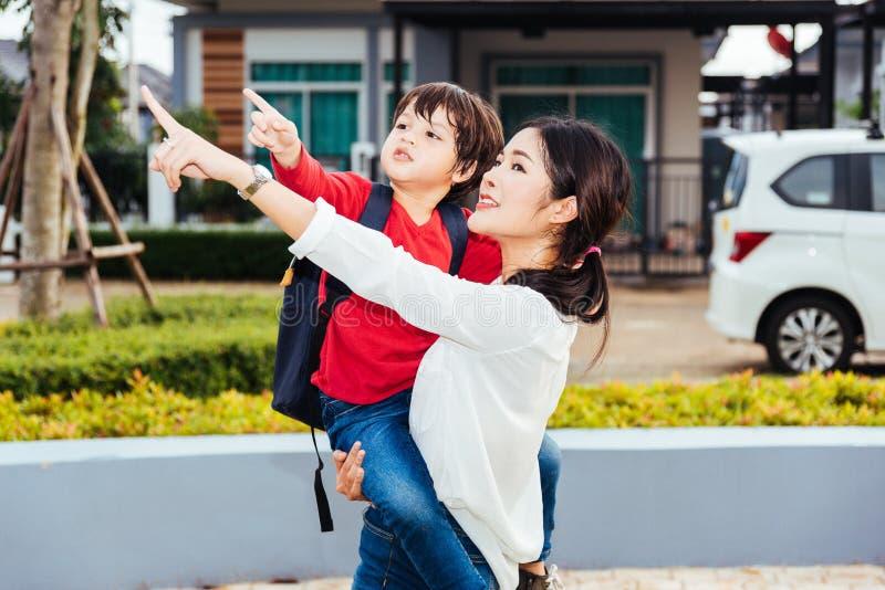 De Aziatische gelukkige moeder die haar jong geitje dragen, het jong geitjepunt deelt uit stock afbeeldingen