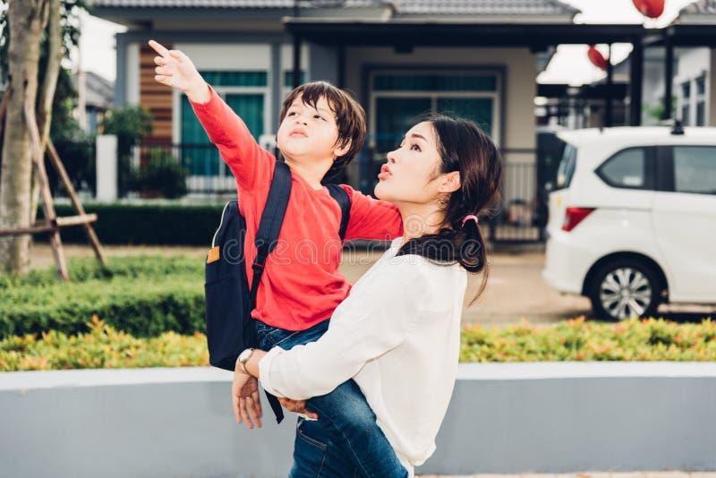 De Aziatische gelukkige moeder die haar jong geitje dragen, het jong geitjepunt deelt uit stock fotografie