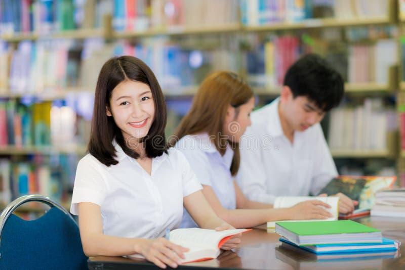 De Aziatische glimlach van de studentendame en gelezen een boek in bibliotheek in universit royalty-vrije stock fotografie