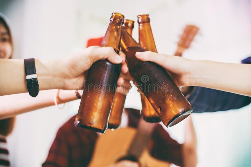 De Aziatische groep vrienden die partij met alcoholisch bier hebben drinkt a stock afbeelding