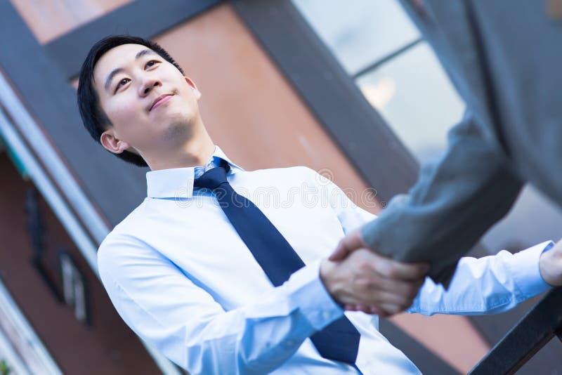 De Aziatische Handen van de Bedrijfsmensenschok met de Een andere Bedrijfsmens stock foto's