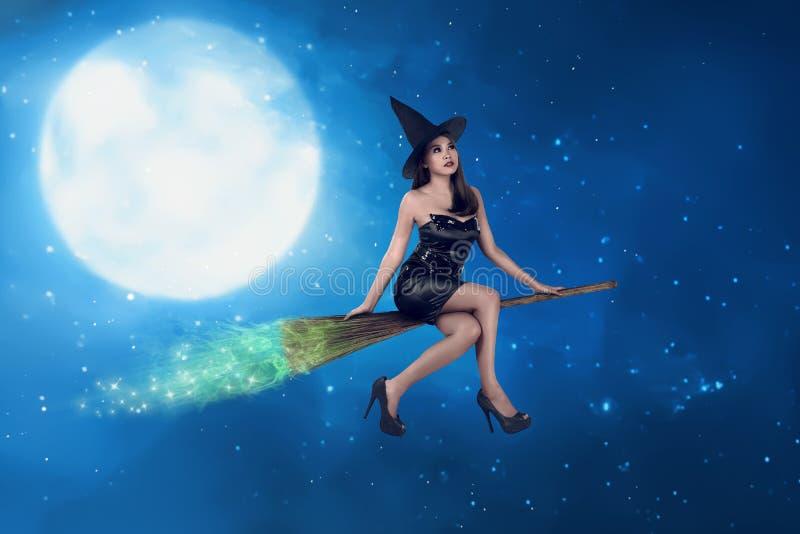 De Aziatische heksenvrouw berijdt de bezem op de hemel royalty-vrije stock fotografie