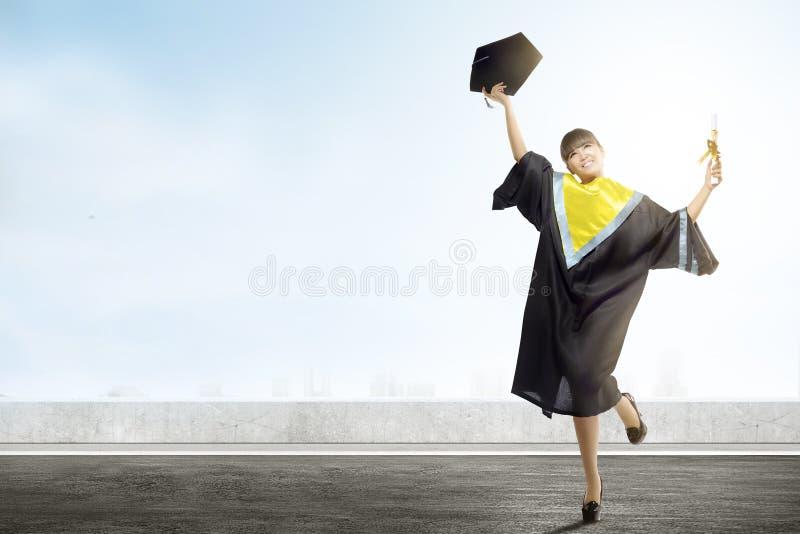 De Aziatische het de barethoed en diploma van de vrouwenholding vieren graduatie van universiteit royalty-vrije stock foto