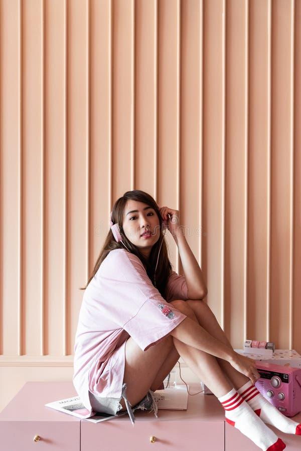 De Aziatische het glimlachen meisjeszitting op roze werkend bureau met oldrose houten streep schilderde muur/comfortabele binnenl stock foto