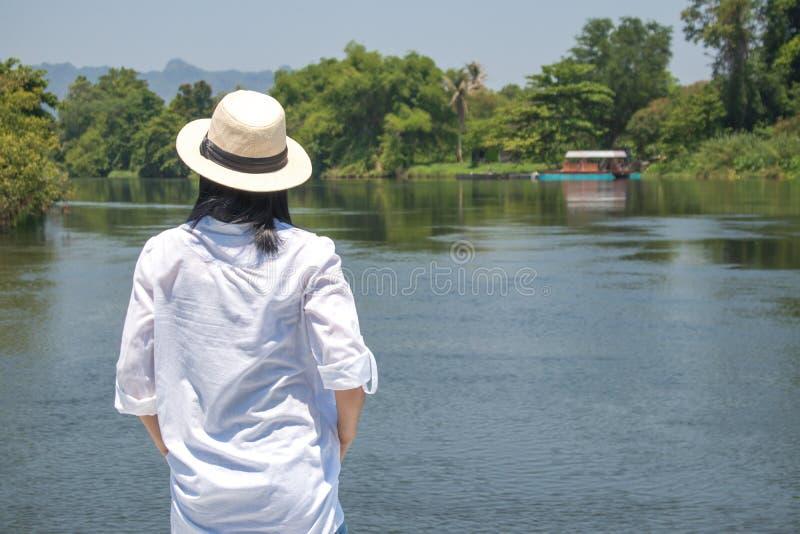 De Aziatische hoed van de vrouwenslijtage en wit overhemd met status op houten brug, zij die zich op rivier verheugen, stock foto's