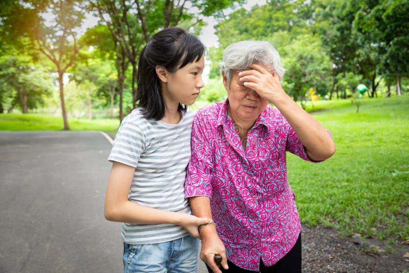 De Aziatische hogere grootmoeder heeft hoofdpijn, wat betreft haar hoofd met haar handen, duizeligheid; duizeligheid; zieke bejaa stock fotografie