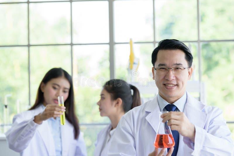 De Aziatische hogere mens die van de laboratoriumwetenschapper bij laboratorium met Aziatische jonge studentenwetenschapper backg stock afbeelding